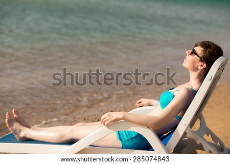 Young slim woman in blue swimwear and sunglasses lying with closed eyes, relaxing on sun deckchair at peaceful sand seashore, tanning in sunlight on hot sea bay, copy space - stock photo