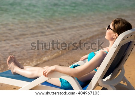 Young slim woman in blue swimwear and sunglasses lying with closed eyes, relaxing on sun lounge at serene sand beach near water, tanning in sunlight of hot sea bay, copy space - stock photo