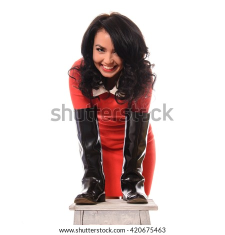 Young slim woman in red dress and brown boots on white background. - stock photo