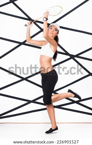 Young slim woman in trendy sportswear playing badminton - stock photo