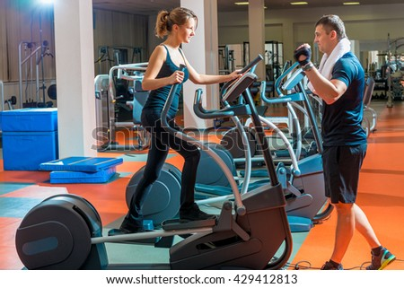Young slim woman is engaged in the simulator and trainer - stock photo