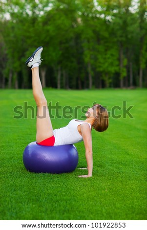 Young slim woman making exercises on fitball, outdoor - stock photo