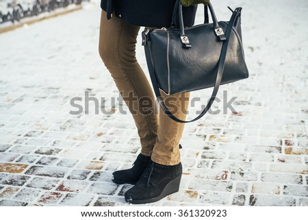 Young slim woman walking in the Park with the purse in the winter. Details of women's clothing. - stock photo