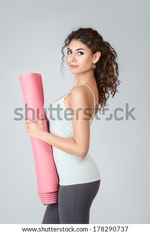 Young slim woman with gymnastics mat over gray background - stock photo