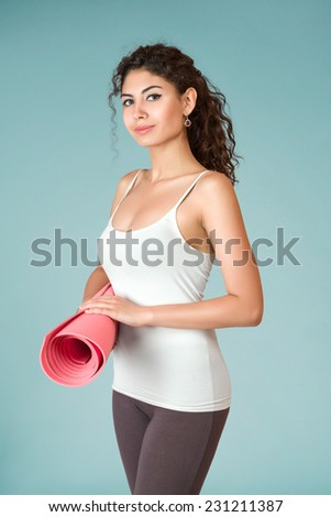 Young slim woman with gymnastics or yoga mat - stock photo