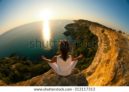 Young slim Yoga woman in zen meditating in warrior pose relaxing outside on top of mountains and sea on sunrise or sunset. Asian fitness model doing yoga on blue sky and blue sea background. - stock photo