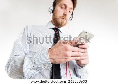 Young smart man listening music and using smartphone - stock photo
