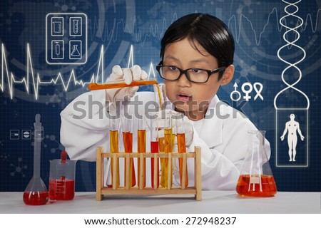 Young smart scientist doing research using chemical liquid in the laboratory - stock photo