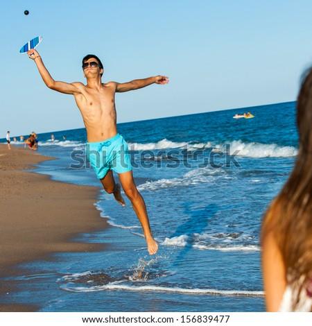 Young smash ball beach tennis player jumping at ball. - stock photo