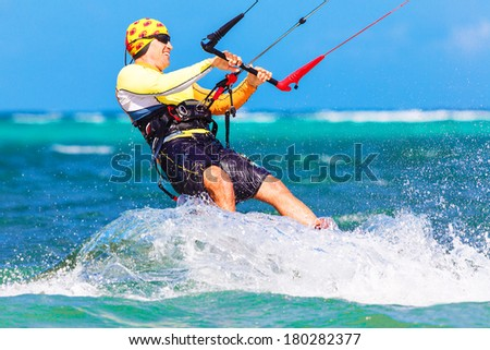 young smiing  kite surfer on tropical sea background Extreme Sport Kite surfing - stock photo