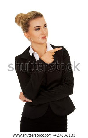 Young smiled businesswoman pointing her finger - stock photo