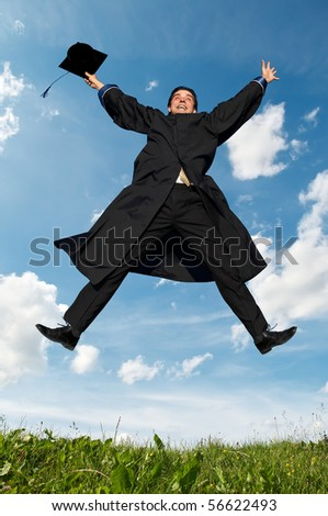 Young smiley graduate student in gown jumping over blue sky - stock photo