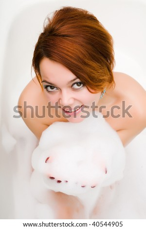young smiley naked woman in bathtub with soapsuds in hands - stock photo