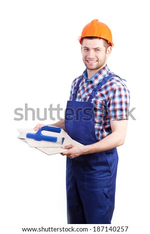 Young smiley tiler preparing tools to work - stock photo