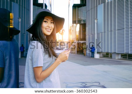Young smiley well-dressed Asian business woman use digital tablet near skyscrapers. Flare light - stock photo