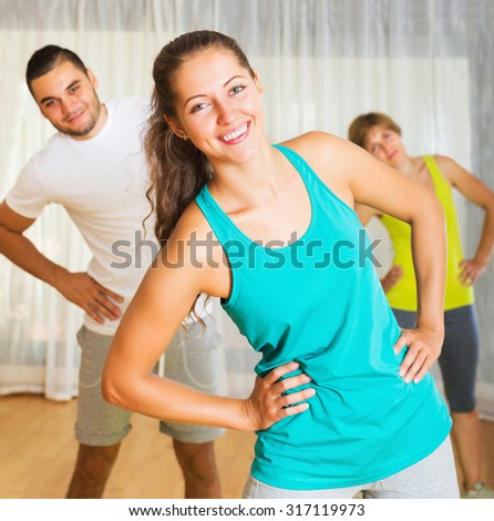 Young smiling active people working in gym - stock photo