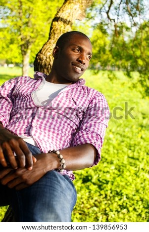 Young smiling african american lying on a tree branch in a park - stock photo