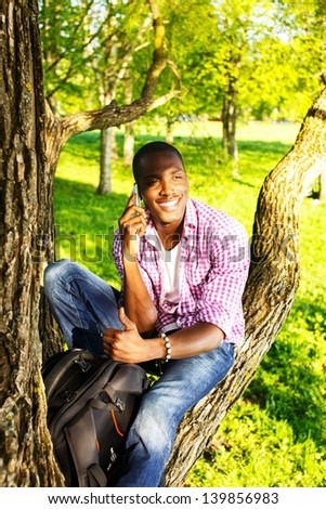 Young smiling african american sitting on a tree in park and calling with mobile phone - stock photo