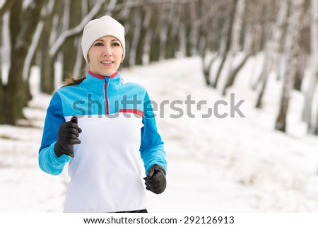 Young smiling athlete woman jogging in winter park. Pretty girl running at winter outdoor with copy space.  - stock photo