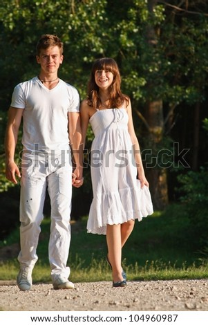 Young smiling attractive couple walking outdoors together - stock photo