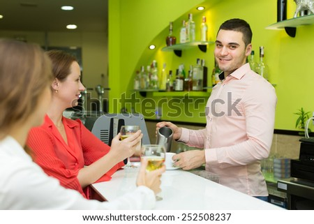 Young smiling bartender and two beautiful girls with wine glasses in hands at bar. Focus on man - stock photo