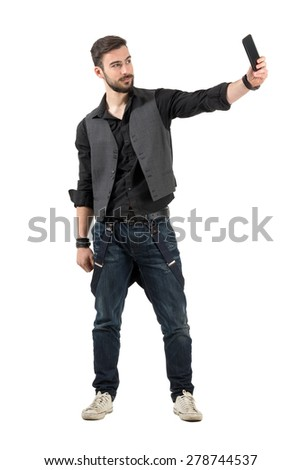 Young smiling bearded hipster taking selfie from high angle. Full body length portrait isolated over white background.  - stock photo