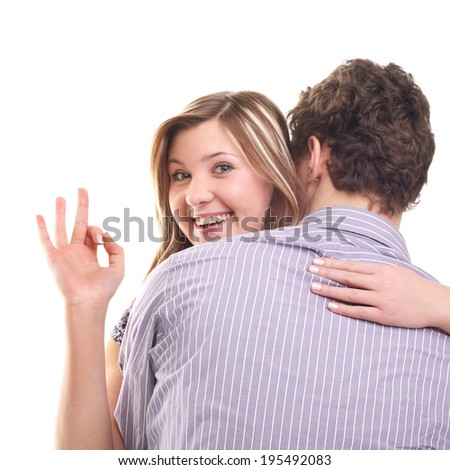 young smiling beautiful blond girl showing ok sign from her boyfriend's back - stock photo