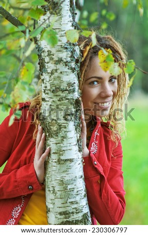 Young smiling beautiful woman with dreadlocks in red clothes near birch. - stock photo