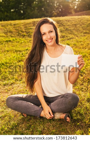 Young smiling beautiful woman with long dark hair is sitting on the grass, holding blank white board - stock photo