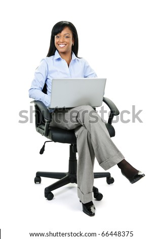 Young smiling black business woman sitting in leather office chair with laptop computer - stock photo