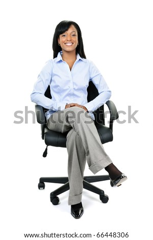 Young smiling black businesswoman sitting in leather office chair - stock photo