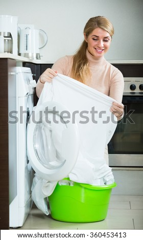 Young smiling blonde with basket of linen near washing machine indoors - stock photo