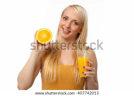Young smiling blonde woman with a glass of orange and an orange in her hands - stock photo