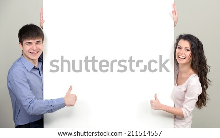 Young smiling boy and girl with white placard. Over light background. - stock photo
