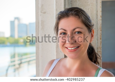 Young smiling brunette in the city, close-up portrait  - stock photo