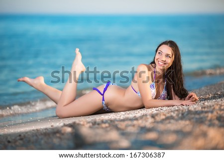Young smiling brunette lying on the beach - stock photo