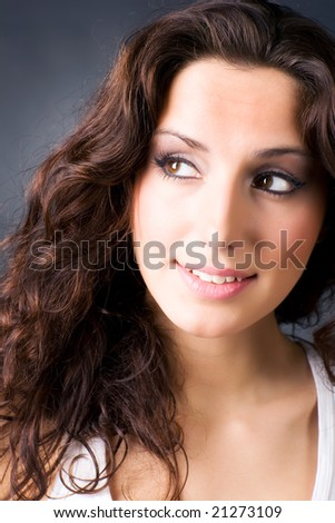 Young smiling brunette woman portrait. On dark background. - stock photo
