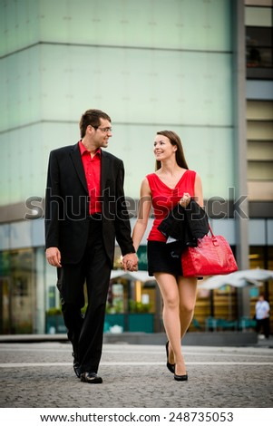 Young smiling business couple walking street after their work - stock photo