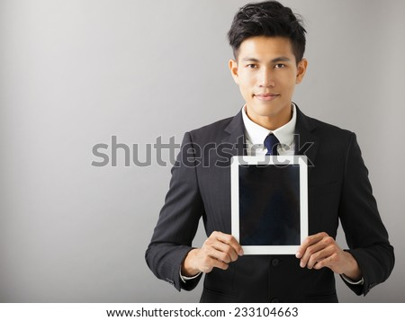 young smiling business man showing tablet pc - stock photo