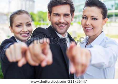 Young smiling business woman and business man. three people pointing something outside - stock photo