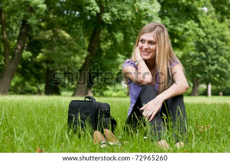 Young smiling business woman siting in grass and relaxing after work - stock photo