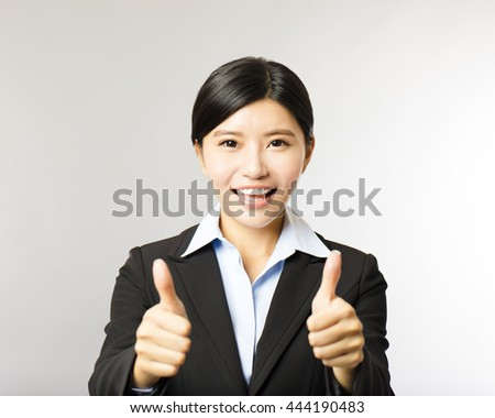 young smiling business woman with thumb up gesture - stock photo
