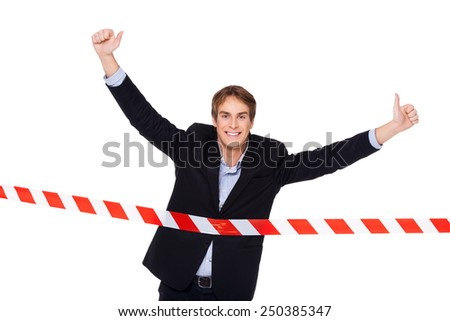 Young smiling businessman crossing finish line with thumbs up. Concept for victory in business - stock photo