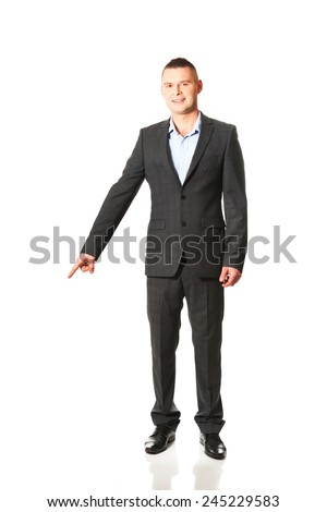 Young smiling businessman pointing down. - stock photo