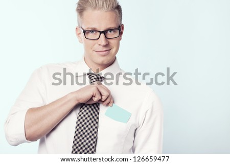 Young smiling businessman putting blank business card with space for text in shirt pocket, isolated. - stock photo