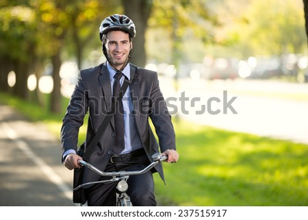young smiling businessman riding a bicycle to work, concept  gas savings concept - stock photo