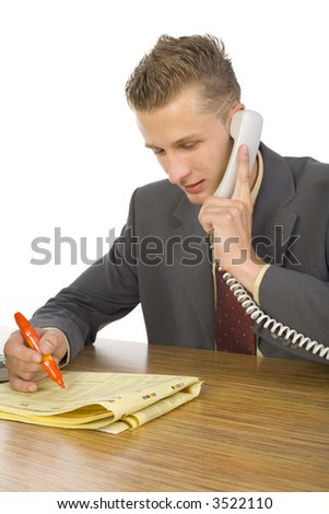 Young smiling businessman sitting at desk, talking on phone and marking something in newspaper. White background - stock photo