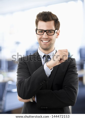 Young smiling businessman standing in office - stock photo
