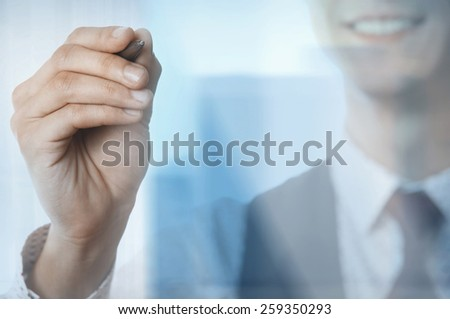 Young smiling businessman with pen behind the glass window - stock photo