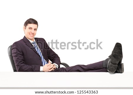 Young smiling businessperson sitting on a chair with his legs up isolated on white background - stock photo